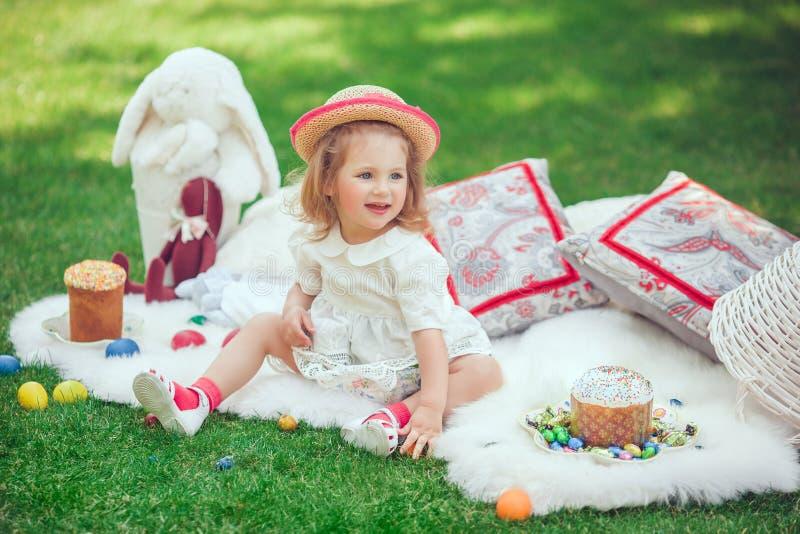 愉快的孩子坐草甸在复活节装饰附近 免版税库存照片