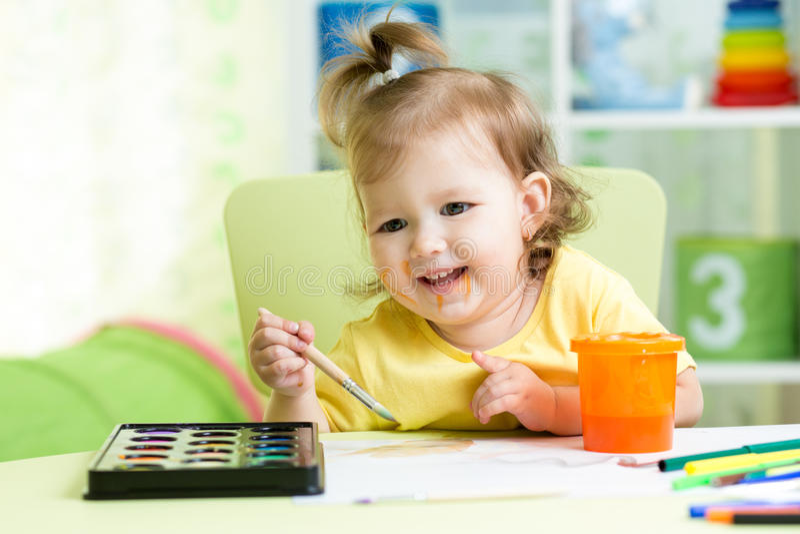 愉快的孩子女孩绘画在托儿所 库存照片