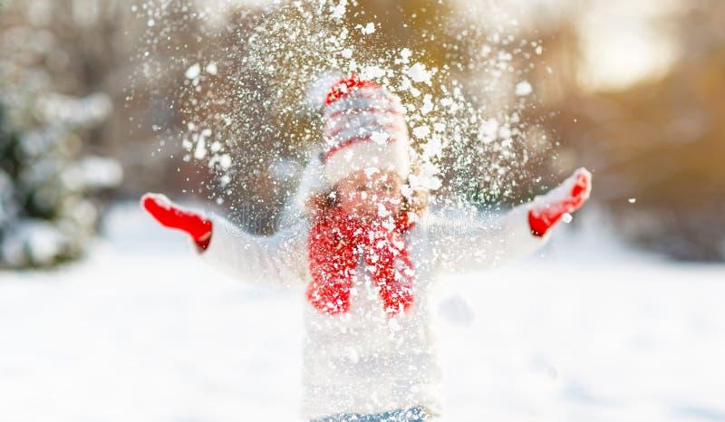 愉快的孩子投掷在冬天步行的雪 免版税库存图片