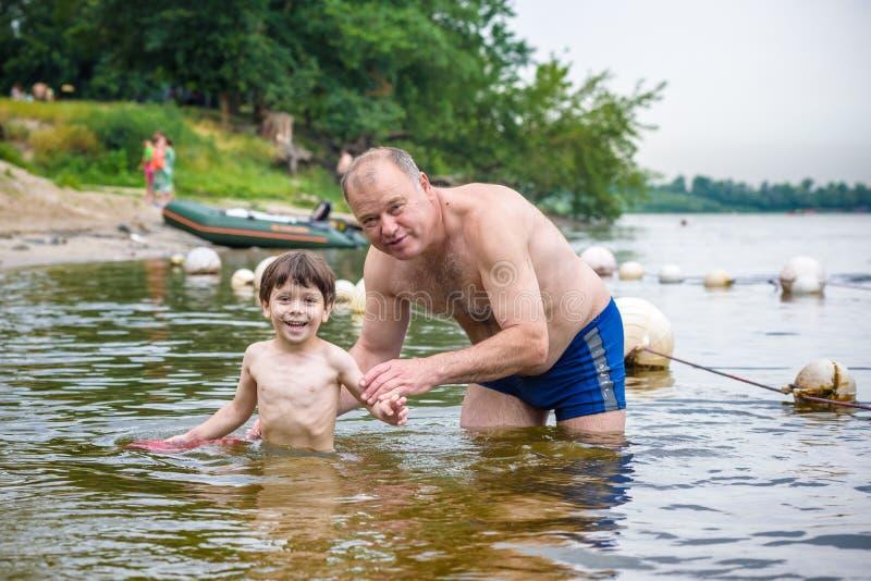 愉快的孩子游泳在湖或河 免版税库存图片