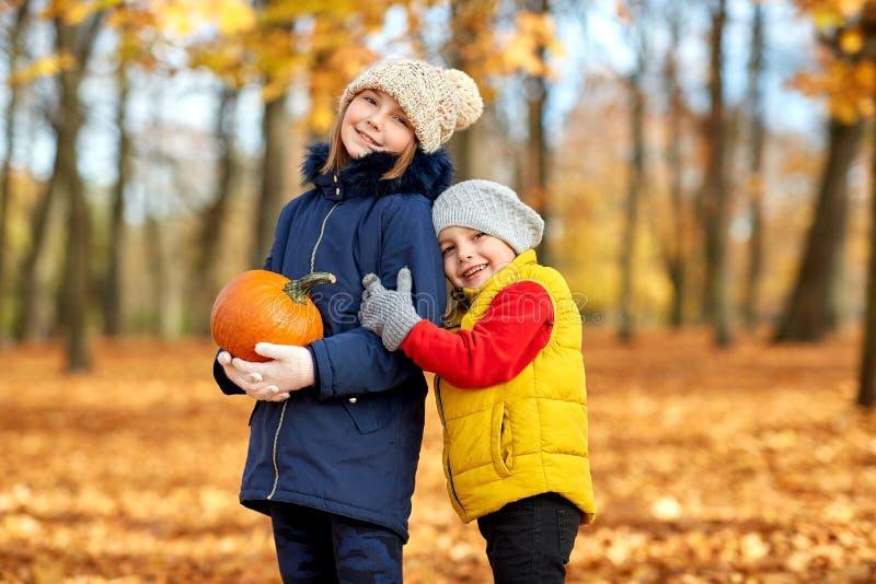 愉快的孩子用拥抱在秋天公园的南瓜 免版税库存照片