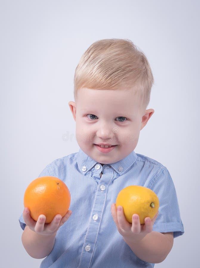 愉快的孩子用桔子 免版税库存照片