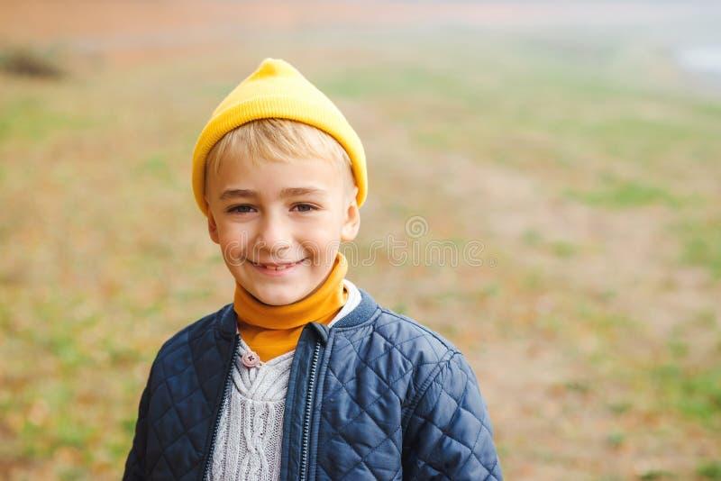 愉快的孩子男孩画象在自然背景的 黄色帽子的时髦的男孩笑和看对照相机的 英俊的微笑的男孩 库存图片