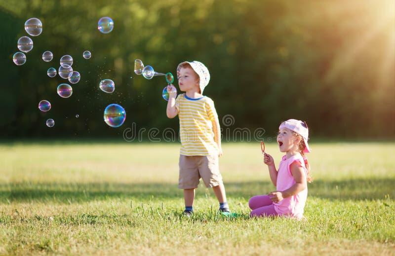 愉快的孩子获得乐趣在草在晴朗的夏天晚上 库存图片