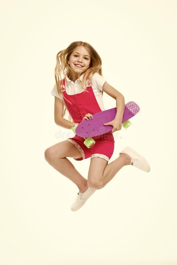 愉快的孩子跳与在白色隔绝的便士板 与滑板的小孩微笑 在行动的乐趣 自由感觉  库存照片