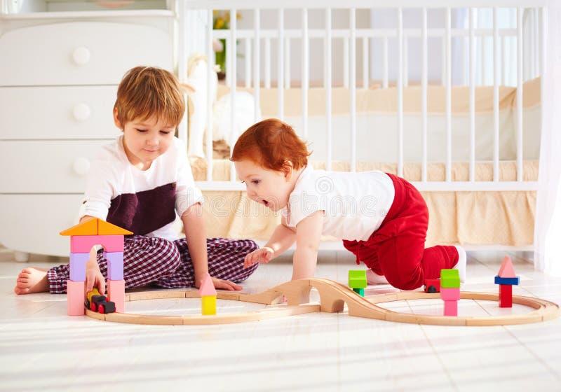 愉快的孩子,使用与木玩具铁路一起的兄弟在托儿所屋子里 免版税库存照片