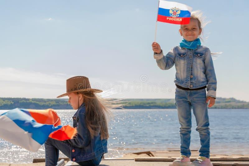 愉快的孩子,有俄罗斯旗子的逗人喜爱的小孩女孩反对一清楚的天空蔚蓝 免版税图库摄影