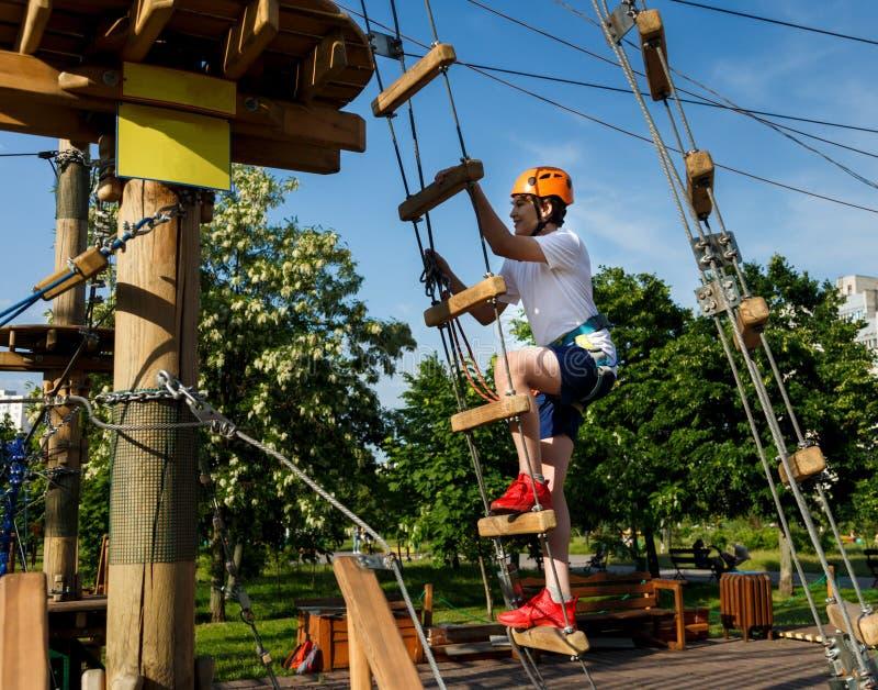 愉快的孩子,橙色盔甲的健康少年男生在一个上升的冒险绳索公园享受活动 免版税库存图片