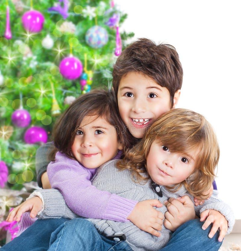 愉快的孩子临近圣诞树 免版税图库摄影