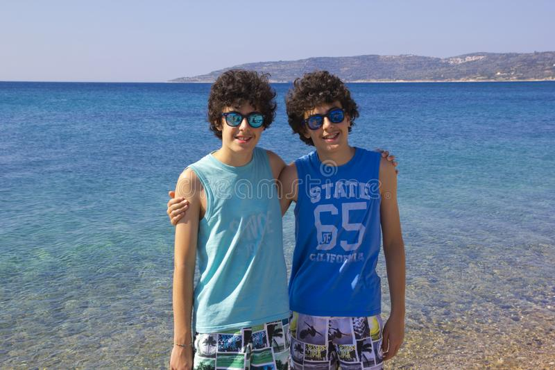 愉快的孪生画象在beachin希腊的 免版税库存照片