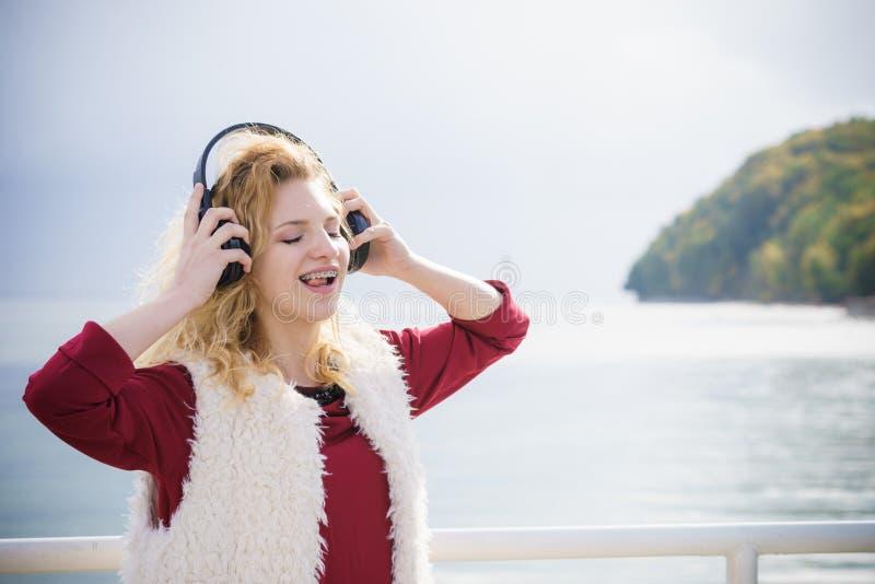 愉快的室外妇女佩带的耳机 免版税库存图片