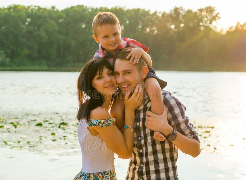 愉快的家庭、妈妈、爸爸和儿子在河附近太阳光芒的  免版税库存图片