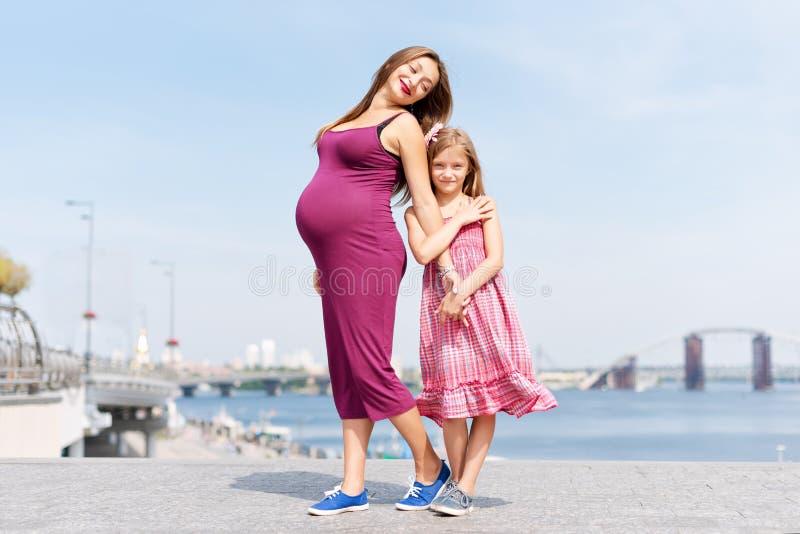 愉快的家庭、怀孕的母亲和她的女儿走和拥抱在堤防的小女孩孩子在夏日 免版税库存图片