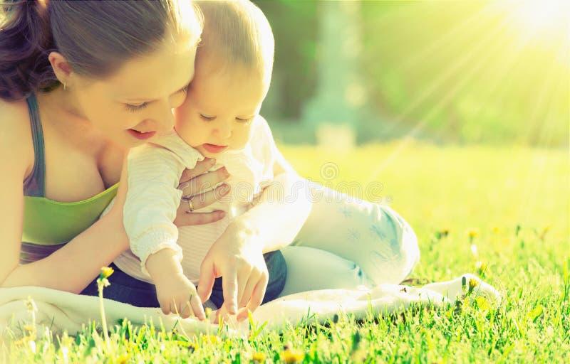 愉快的家庭。妈妈和婴孩在一个草甸在夏天在公园 免版税库存图片