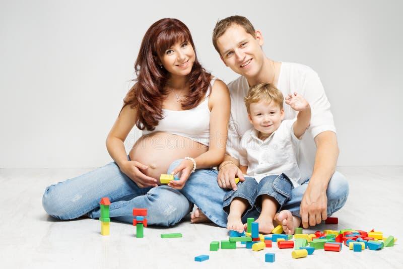 愉快的家庭。有演奏玩具块的孩子的父母 库存照片