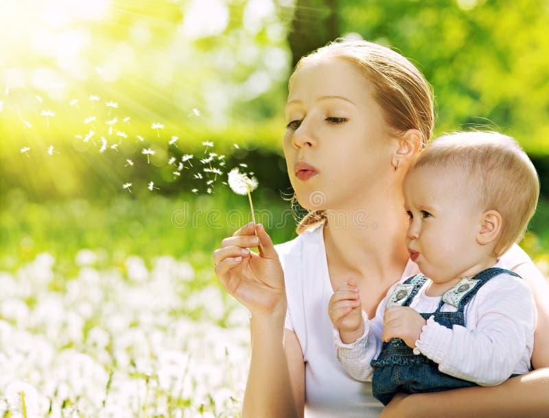 愉快的家庭。母亲和吹在蒲公英的女婴开花 库存照片