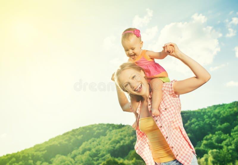 愉快的家庭。母亲和女儿使用在自然的女婴 免版税图库摄影
