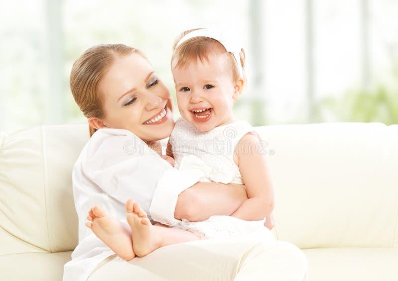 愉快的家庭。母亲和小女儿戏剧,拥抱,亲吻 免版税库存图片