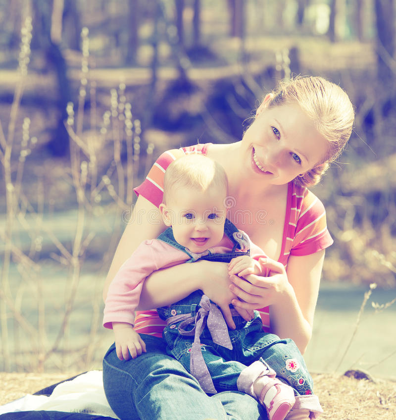 愉快的家庭。母亲和婴孩步行的在公园自然的 库存图片