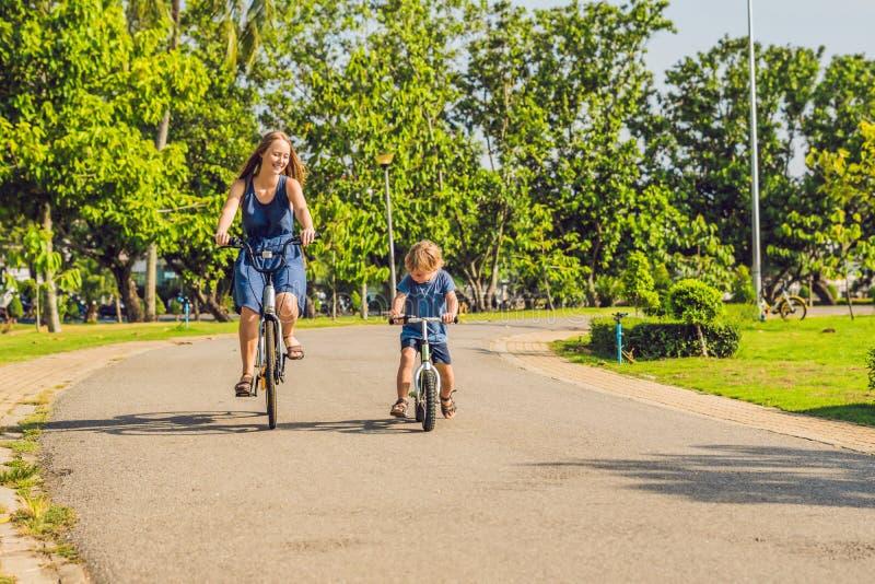 愉快的家庭乘坐自行车户外和微笑 一个自行车和儿子的妈妈balancebike的 库存照片