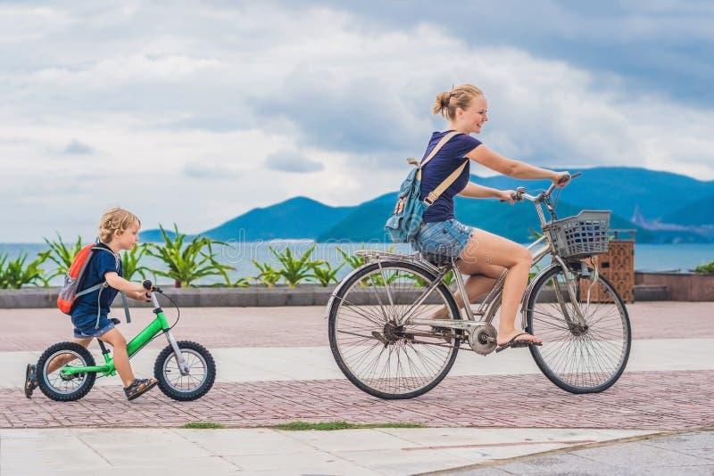 愉快的家庭乘坐自行车户外和微笑 自行车的妈妈 免版税库存照片