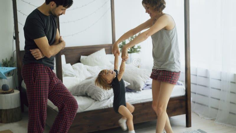 愉快的家庭和小的逗人喜爱的女儿跳舞和在家转动在近的床附近在卧室 库存照片