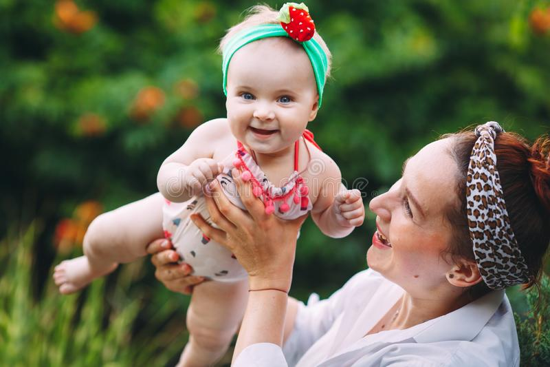 愉快的家庭和平户外 母亲投掷婴孩,笑和使用在自然的夏天 免版税库存照片
