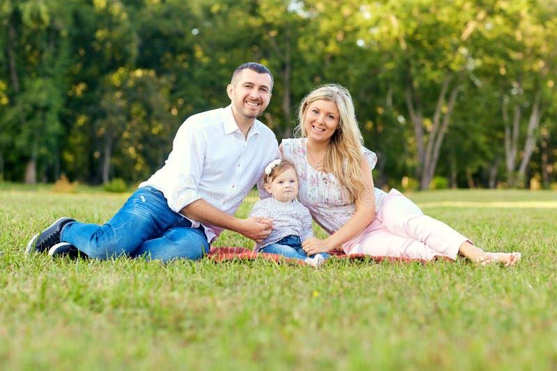 愉快的家庭在一个公园在夏天秋天 小父亲母亲 免版税库存图片