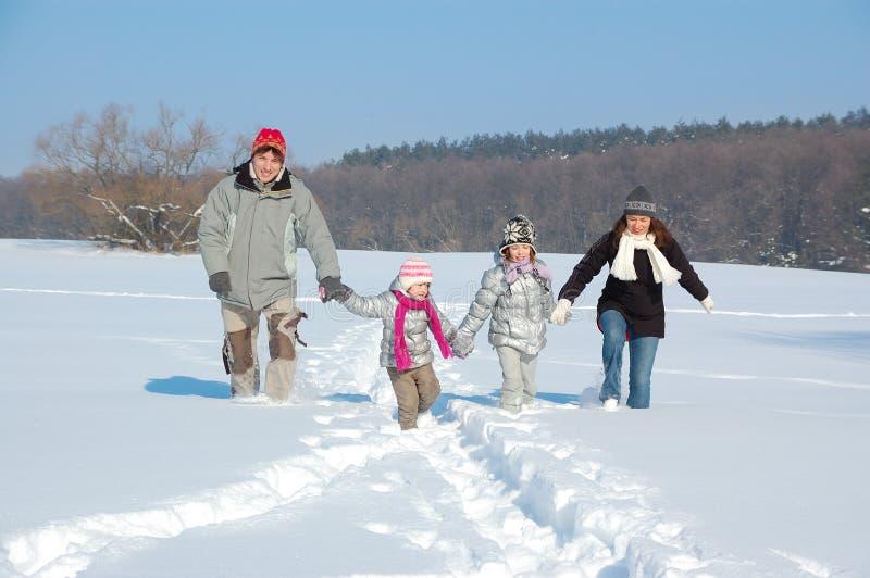 愉快的家庭在冬天,获得乐趣和使用与雪户外假日周末 免版税库存照片