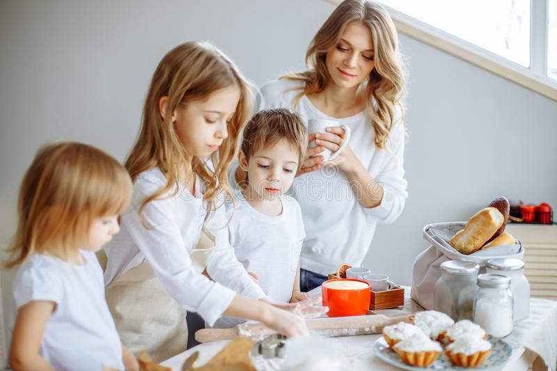愉快的家庭在厨房里 母亲和她逗人喜爱的孩子烹调曲奇饼 图库摄影