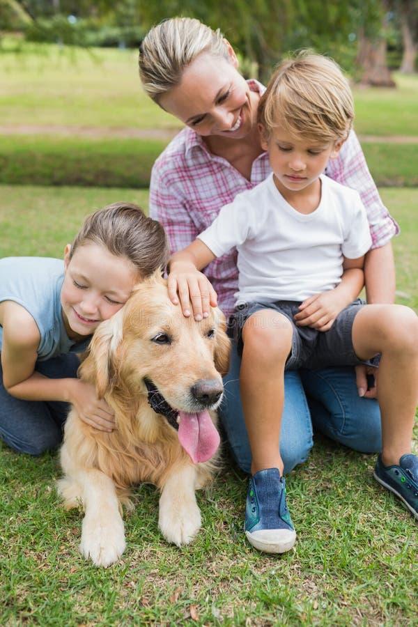 愉快的家庭在有他们的狗的公园 库存照片