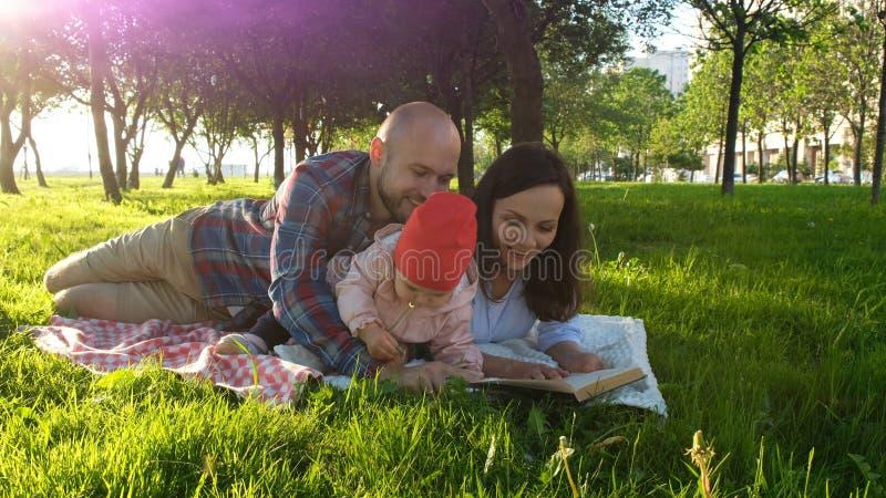 愉快的家庭在草说谎并且读了与孩子的书在野餐和戏剧在日落在公园 免版税库存照片