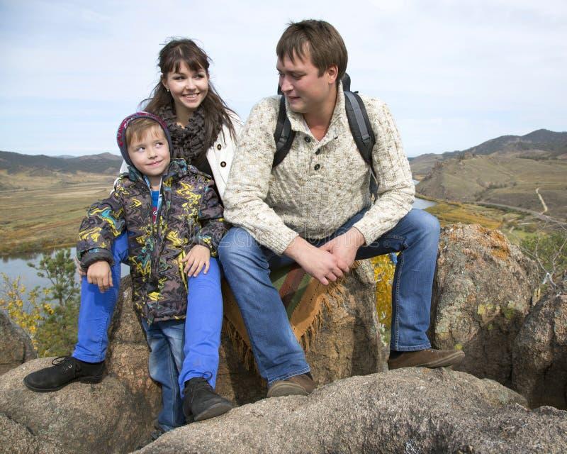 愉快的家庭坐石头 库存图片