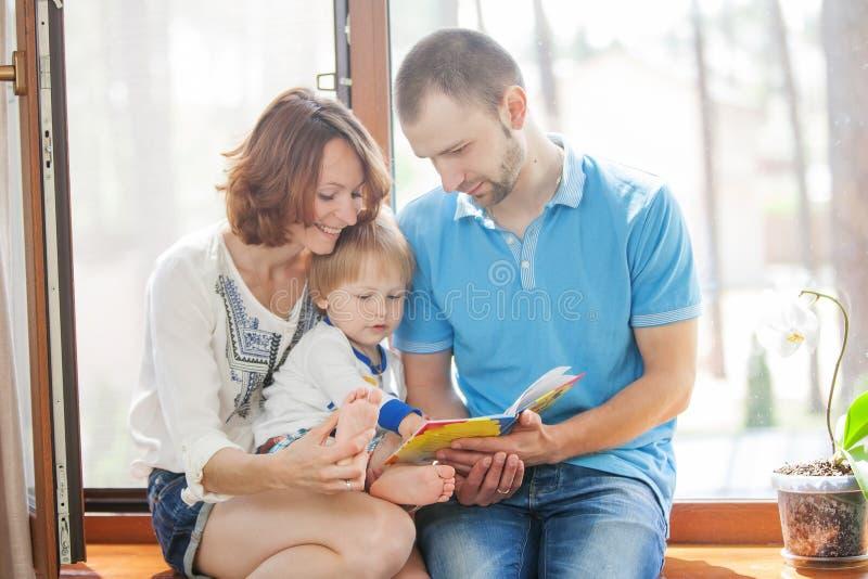 愉快的家庭坐窗台 库存图片