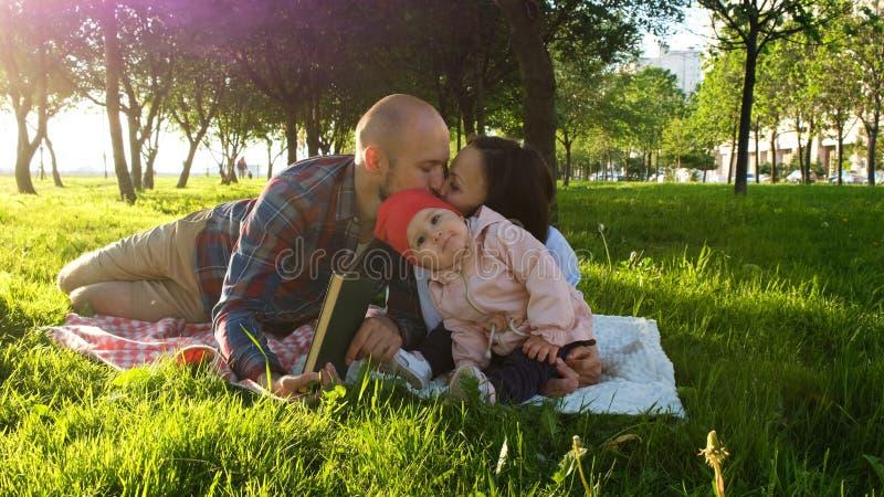 愉快的家庭基于与孩子的自然在日落在公园 父母亲吻 免版税图库摄影