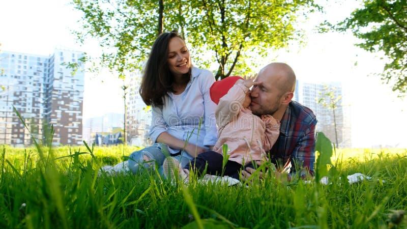愉快的家庭基于自然 父母使用与一个小儿童女儿在一个公园在夏天在日落 免版税库存图片