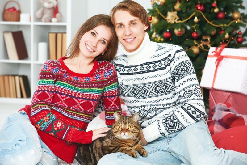 愉快的家庭夫妇和猫在圣诞节在家 库存图片