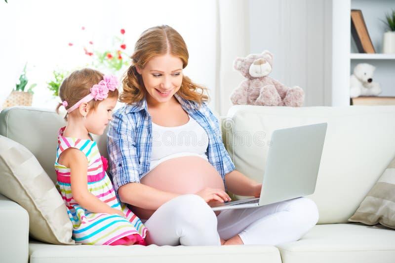 愉快的家庭孕妇和孩子有膝上型计算机的在家 免版税库存图片