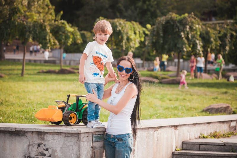 愉快的家庭年轻花费时间的母亲和她五岁的儿子室外在一个夏日 免版税图库摄影