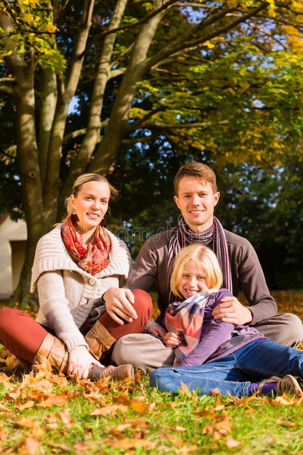 愉快的家庭户外坐草在秋天 免版税库存图片
