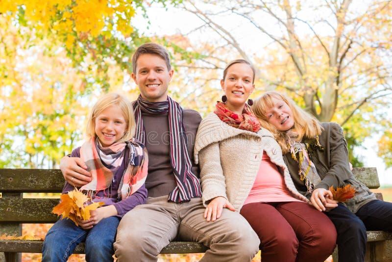 愉快的家庭户外坐长凳在秋天 免版税库存图片
