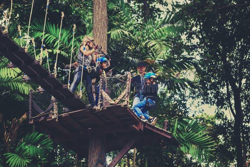 愉快的家庭旅行游人享受在一个受欢迎的旅游胜地,长臂猿的飞行的一次扣人心弦的旅途 免版税库存照片