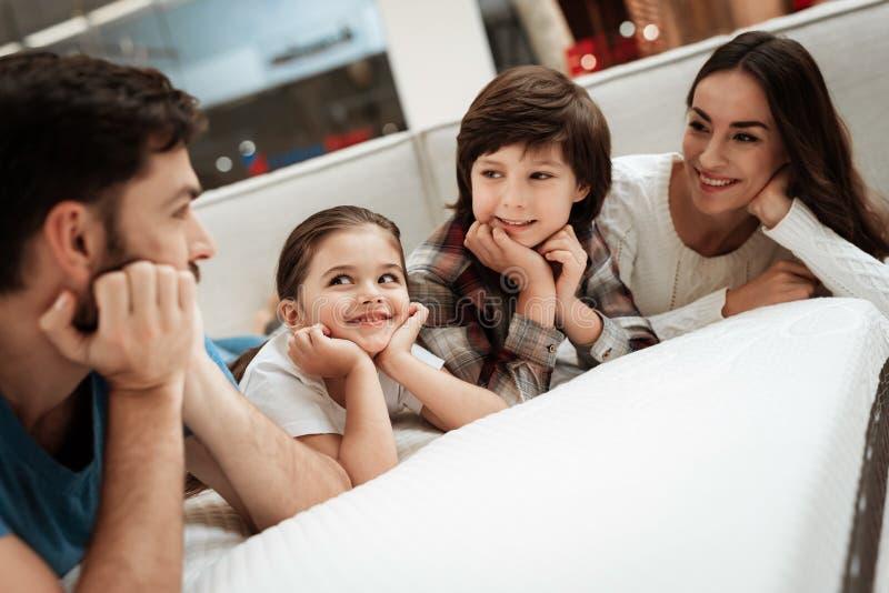 愉快的家庭是松弛在矫形家具店的床垫 大家庭一起检查床垫的软性 库存图片