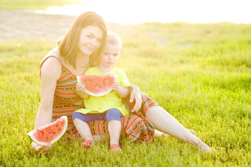 愉快的家庭有在绿草的野餐在公园 免版税图库摄影