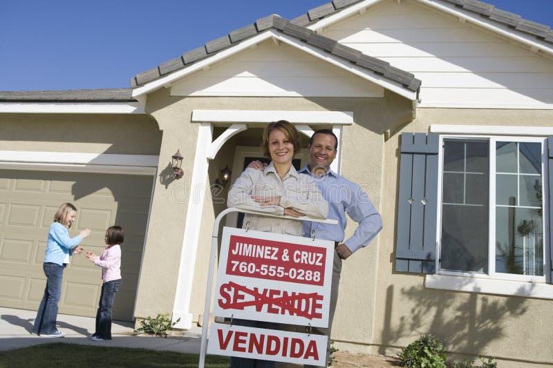 愉快的家庭有被卖的标志的家外 免版税库存照片