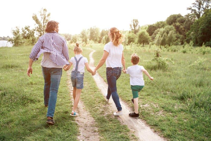 愉快的家庭步行沿着向下路在草甸 父母用人工拿着他们的孩子 他们跳并且享用 库存图片