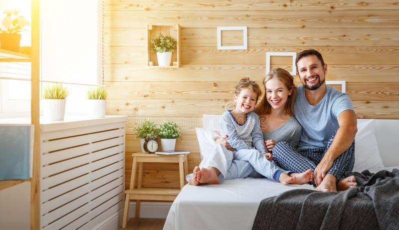 愉快的家庭母亲、父亲和儿童笑在床上 库存照片