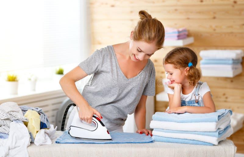 愉快的家庭母亲主妇和儿童女儿电烙的衣裳 免版税库存照片