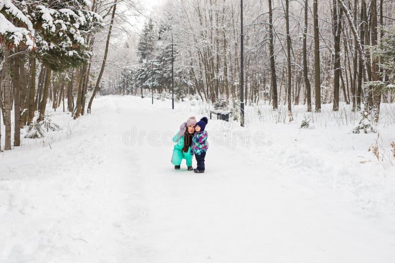 愉快的家庭母亲和使用和笑在冬天的女婴女儿户外在雪 免版税库存照片