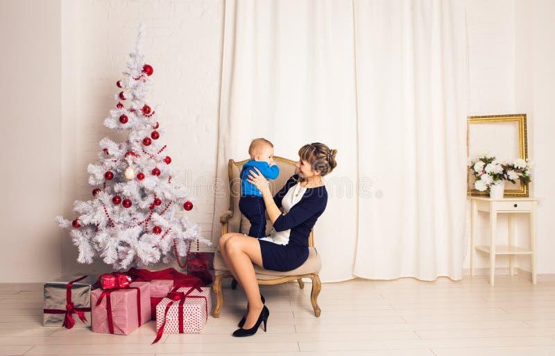 愉快的家庭母亲和使用在家圣诞节假日的婴孩小儿子 新年` s假日 有妈妈的小孩的 库存图片